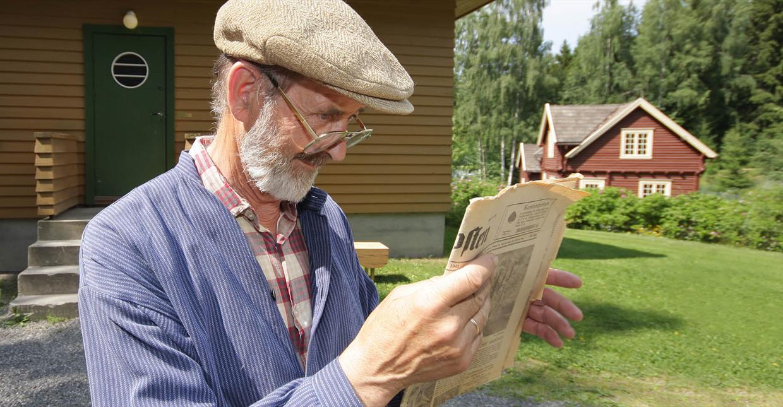 Mann leser avis på Maihaugen