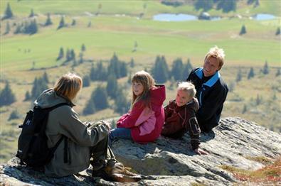 Familie med 2 barn og 2 voksne som raster på fjelltopp under vandretur
