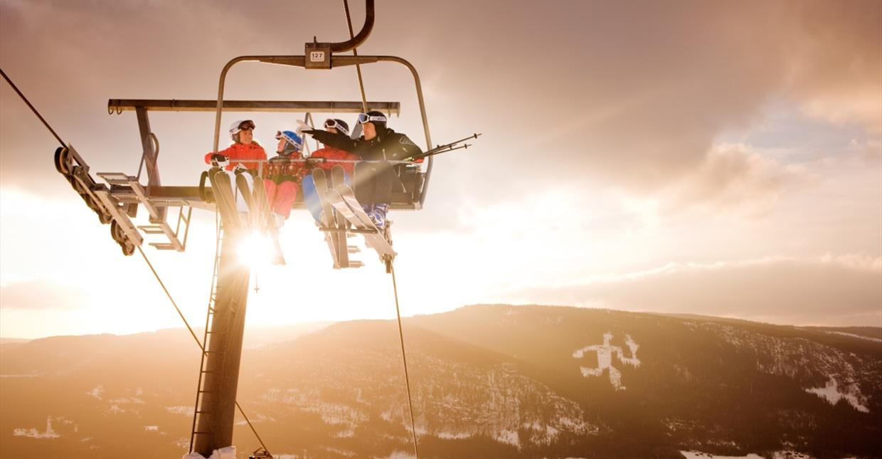 Alpine skiers in chair lift in Hafjell
