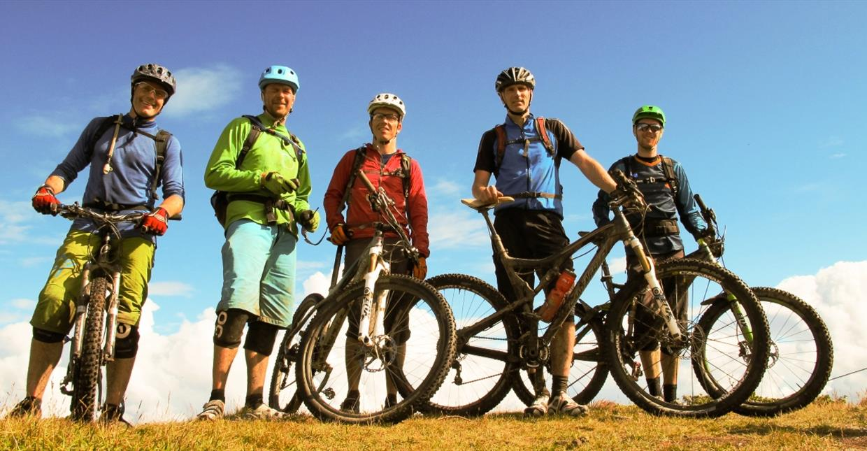 Five single track cyclist standing on a mountain ridge at Skeikampen