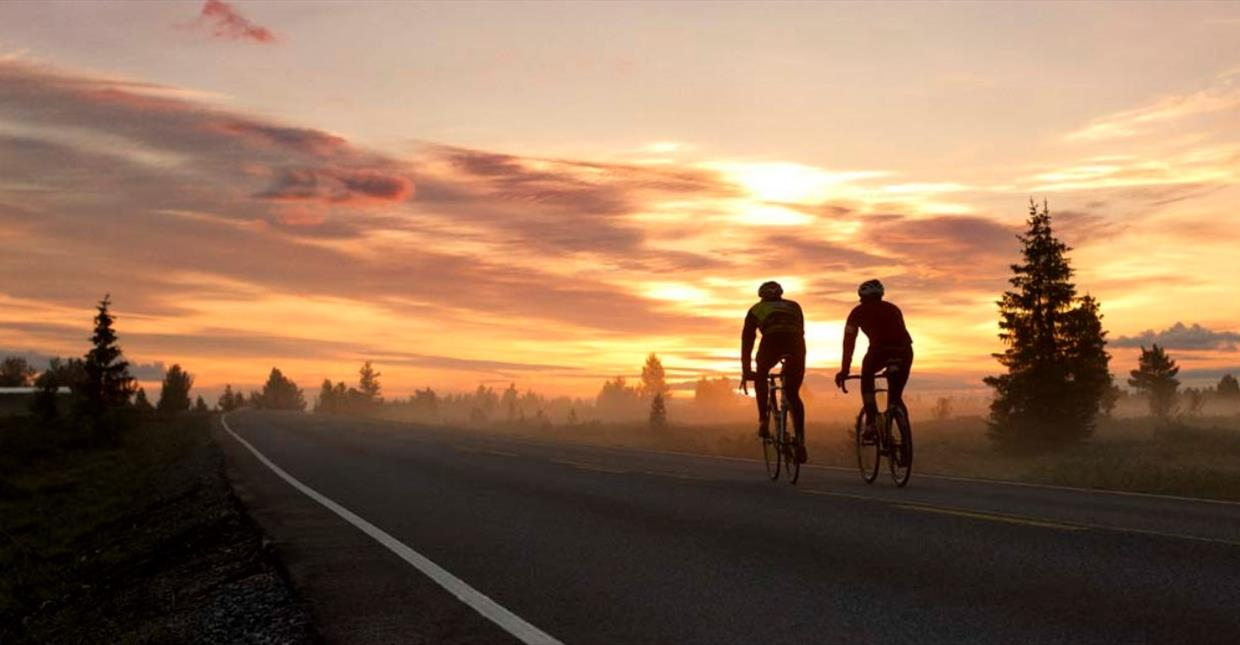 Road Bikers on a mountain platou in sun set.