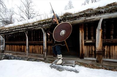 Man in old costume with sheild and spear in front of an old timber building.